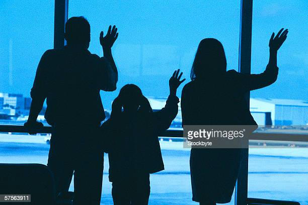 silhouette of a family waving through a window