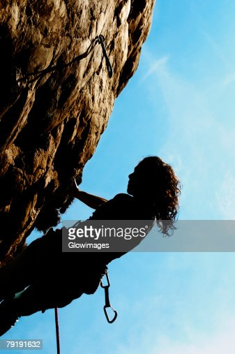 Silhouette of a female rock climber holding onto a rock with the help of a rope : Foto de stock