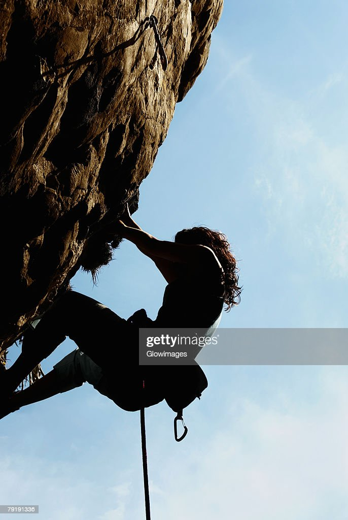 Silhouette of a female rock climber scaling a rock face : Foto de stock