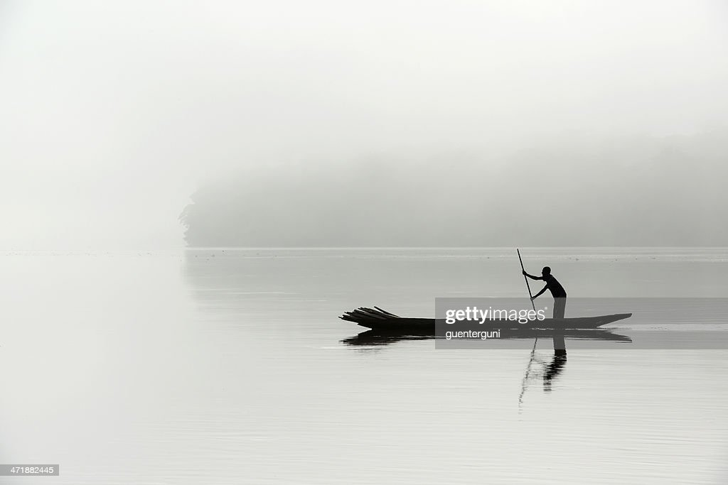 Silhouette of a fisherman in the morning fog, Congo river