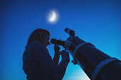 Silhouette of a girl and telescope with Moon on the sky. My astronomy work.