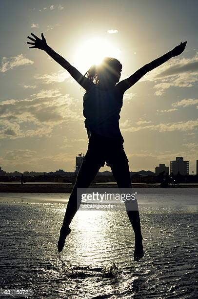 Silhouette of a girl jumping in the air on the beach