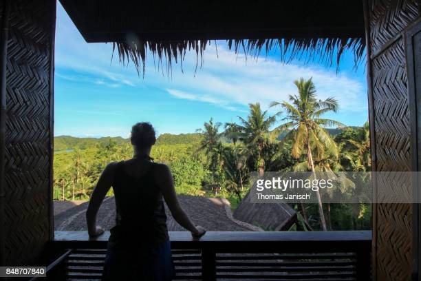 Silhouette of a girl looking from a terrace to the tropical island of Palau