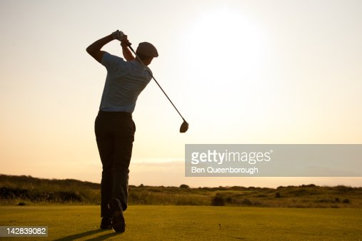 Silhouette of a golfer teeing off : Stock Photo