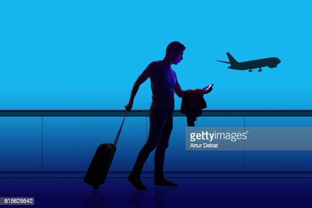 Silhouette of a guy checking his smartphone ready to departure on a airport at night with illustration effect during a travel with trolley suitcase using application technology to get information about the trip.