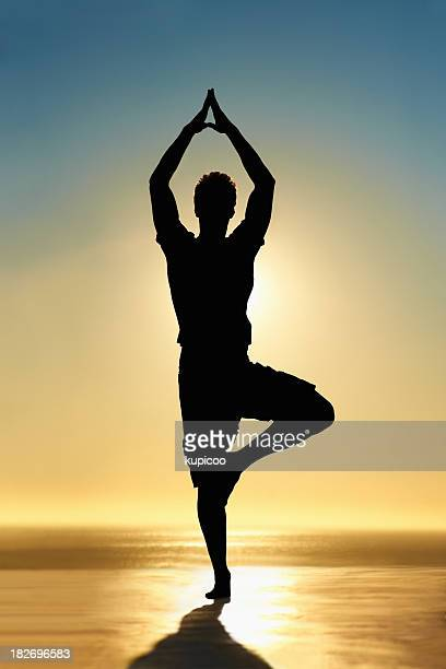 Silhouette of a guy doing yoga at sunrise