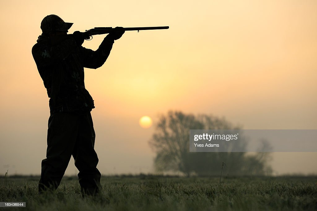 Silhouette of a hunter aiming his shotgun