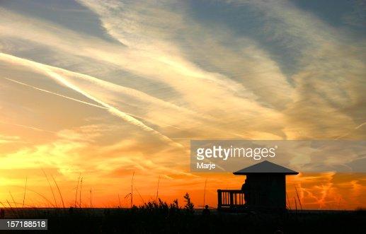 Silhouette of a hut against a beach sunset
