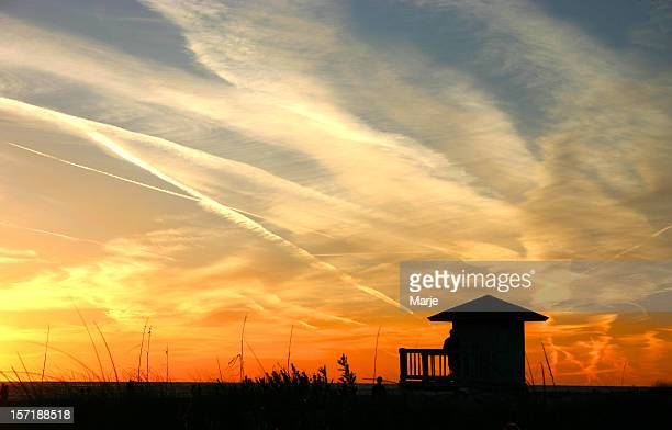 Silhouette of a hut against a beach sunset