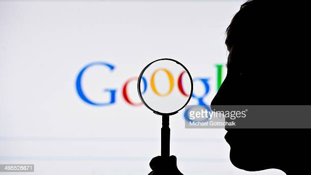 A silhouette of a man and a magnifying glass is seen in front of a screen on which the Google search engine is displayed on June 02 2014 in Berlin...