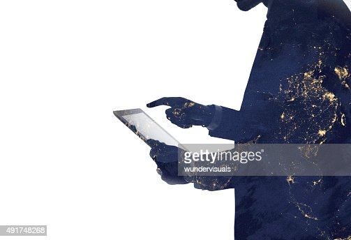 Silhouette of a man and digital tablet with galaxy overlaid