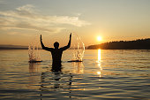 Silhouette of a man at sunset background. The guy on the waist plunged into the sea. Splashes water by hand.