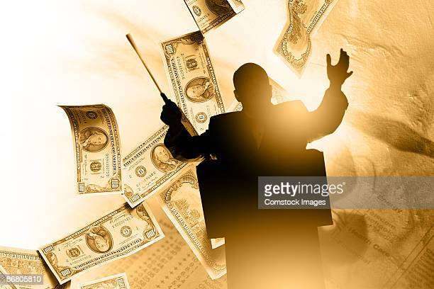 Silhouette of a man conducting music with money in background