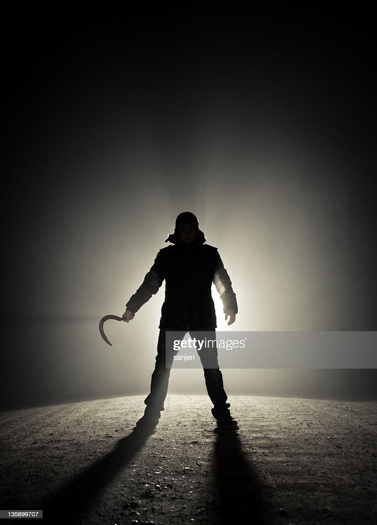 Silhouette of a man in an alley holding a sickle in his hand