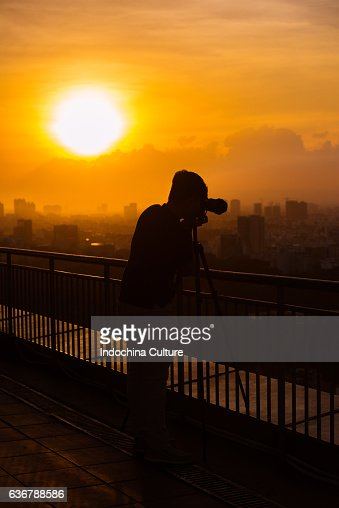 A silhouette of a man outside with a camera at sunset.