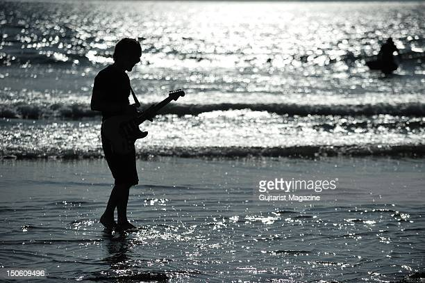 Silhouette of a man paddling in water playing a Fender Stratocaster electric guitar session for Guitarist Magazine taken on July 1 2011