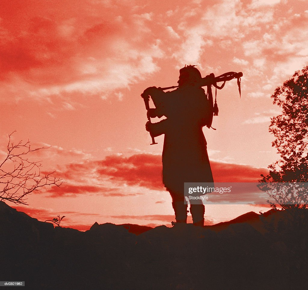 Silhouette of a Man Playing Bagpipes