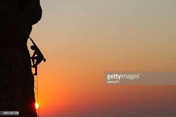 Silhouette of a man rock climbing at sunset