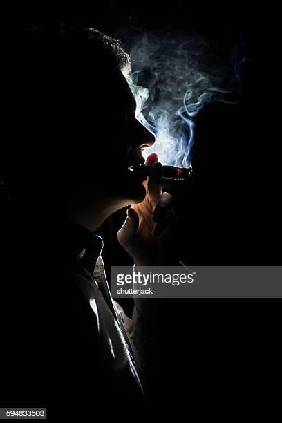 Silhouette of a man smokinga cigar