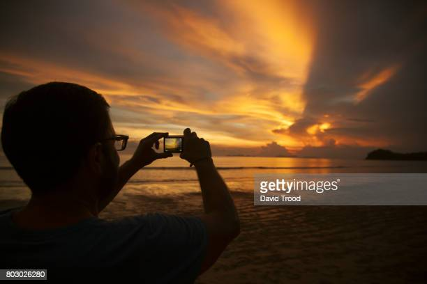 Silhouette of a man taking a photo of the sunset