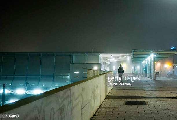 Silhouette of a man walking early on a foggy night in an urban setting