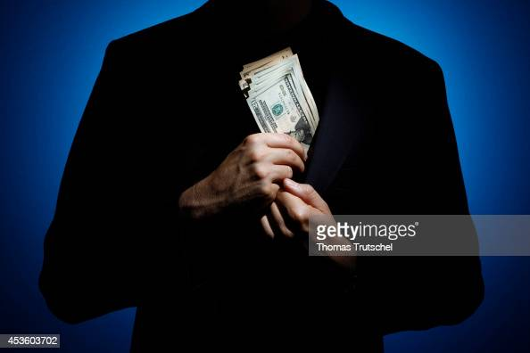 Silhouette of a man who puts a large bundle of banknotes in his jacket on August 06 in Berlin Germany