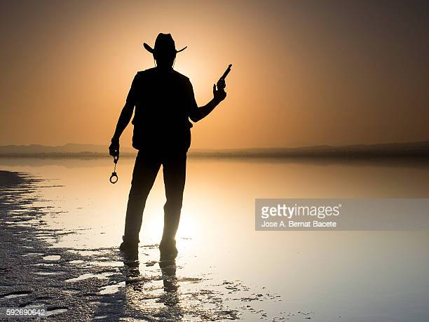 Silhouette of a man with cowboy clothes and pistoala front of a lake