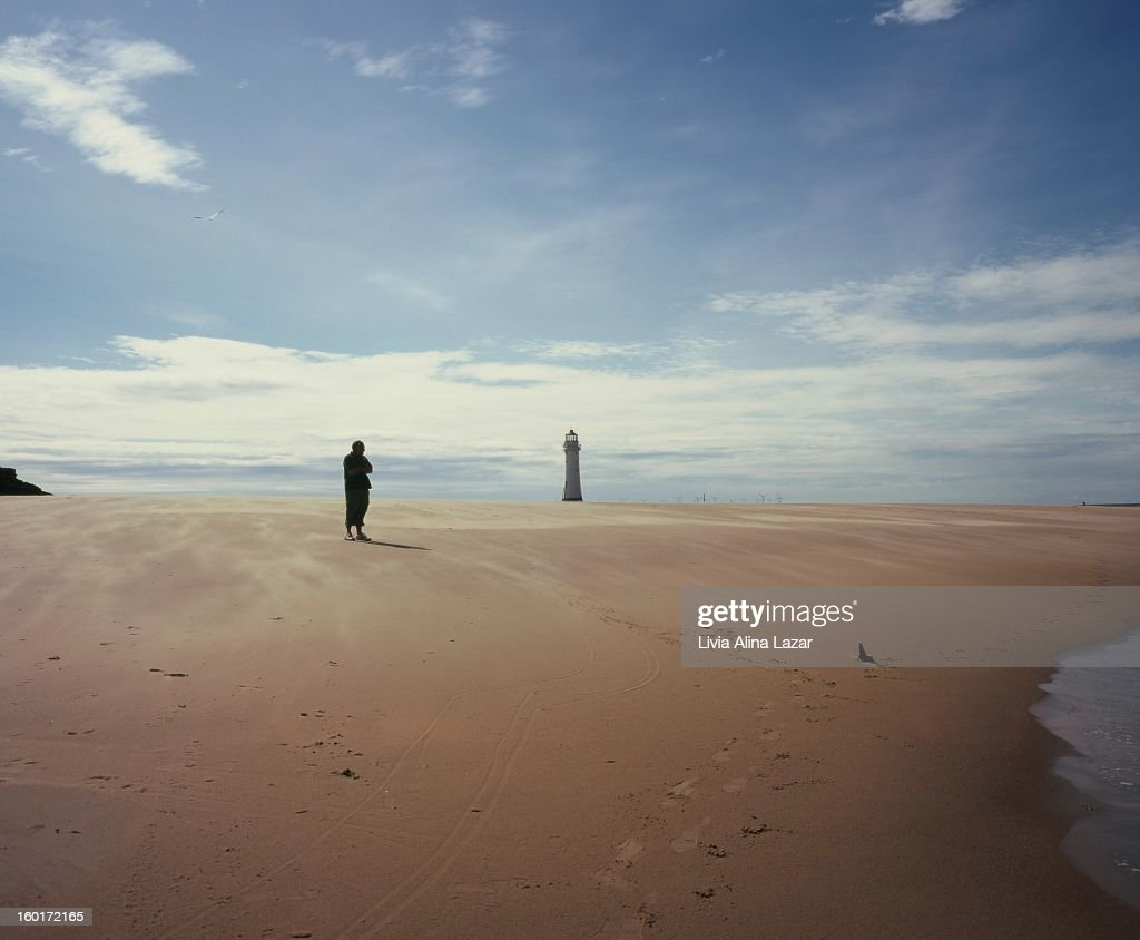 CONTENT] Silhouette of a meditative man on the shore; sand beach with a lighthouse. New Brighton.
