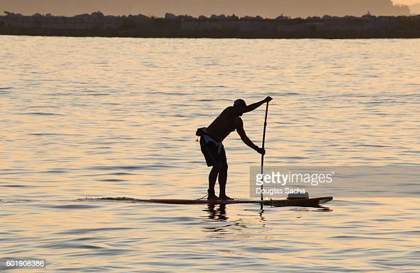 Silhouette of a paddleboarder struggling to navigate the surf board
