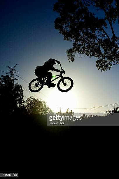 Silhouette of a person doing a stunt on a BMX bicycle