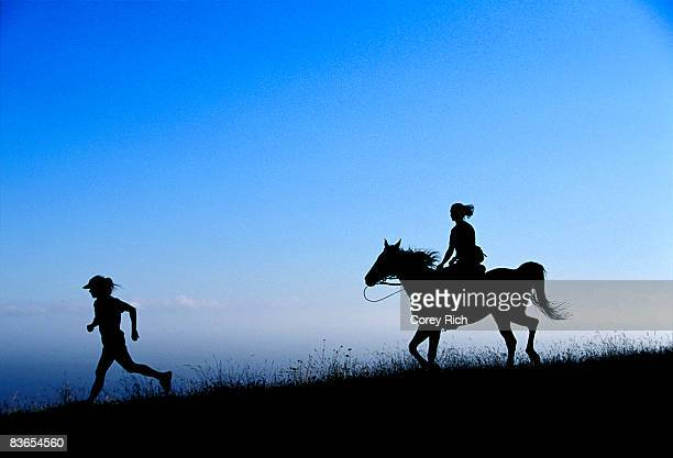 Silhouette of a person running with another person riding a horse behind.