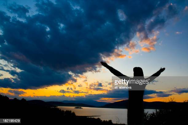 Silhouette of a person with outstretched arms at sunset