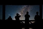 Silhouette of a photographers group who shoots the Landscape of Milky way over reservoir with mountain and deep forest at night sky