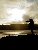 silhouette of a pirate pointing out to sea. Dramatic cloudy sky in background