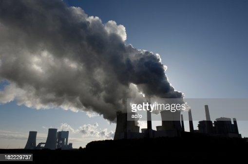 Silhouette of a power plant with pollution