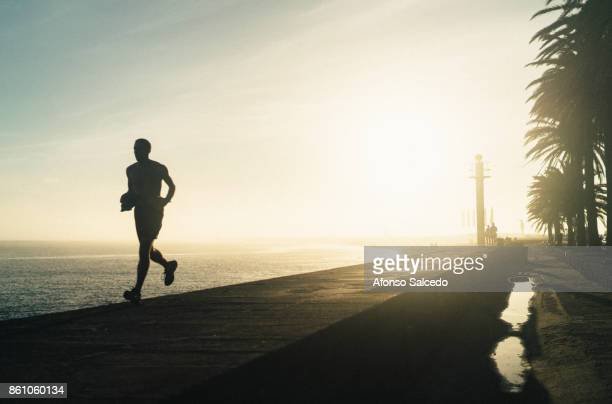 Silhouette of a runner towards the camera during Sunset by the Douro River