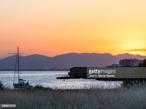 Silhouette of a sailboat in the sea near a harbor, during a sunset between the mountains on the island of Tabarca, Spain