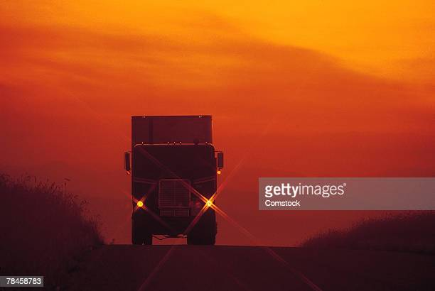 Silhouette of a semi-truck at sunset