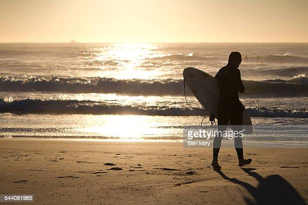 Silhouette of a surfer walking towards beach
