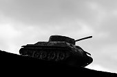 Silhouette of a tank against a background of dark clouds sky. The Second World War. 1939-1945. 9-th of May. Great Victory Day. The concept of war of the army of political conflict