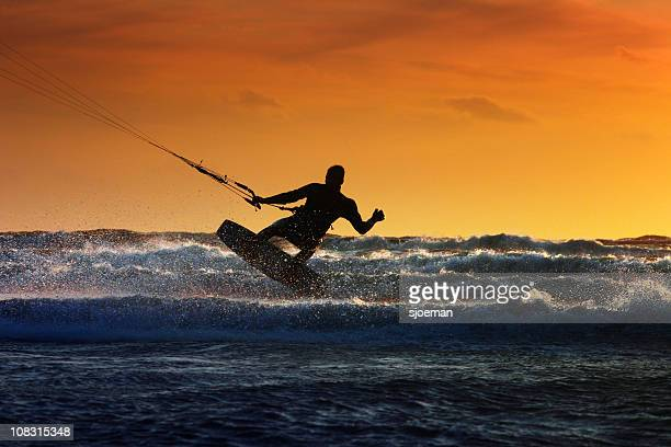 Silhouette of a windsurfer riding along the waves