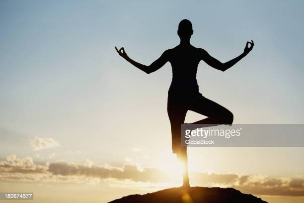 Silhouette of a woman in meditative pose at sunrise
