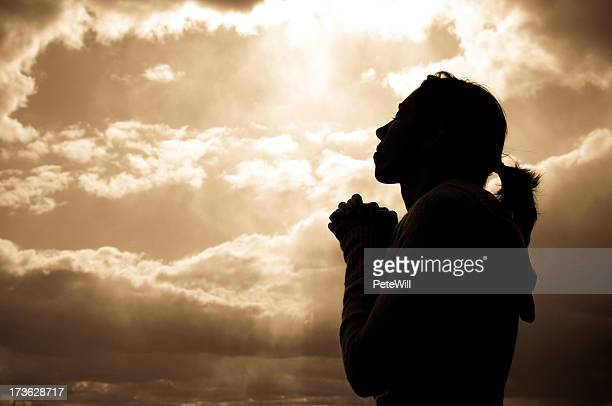 Silhouette of a woman looking at the sky, praying