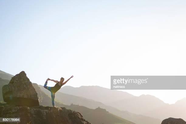 Silhouette d'une femme à pratiquer le Yoga sur les rochers