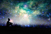 Silhouette of a woman sitting outside, starry night background - NASA elements are included