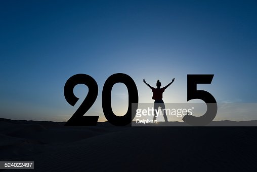 2015, silhouette of a woman standing in the sunrise : Stock Photo
