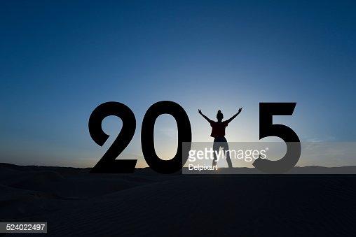 2015, Silueta de una mujer de pie en la puesta de sol : Foto de stock