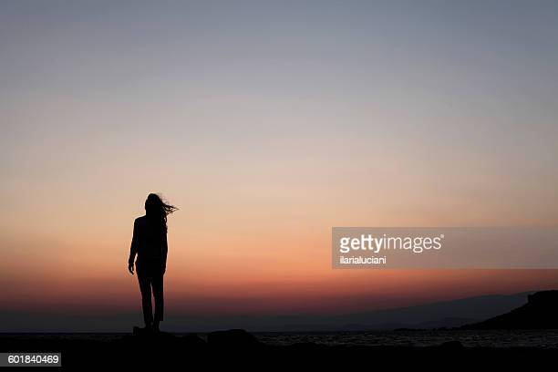 Silhouette of a woman standing outdoors at sunset