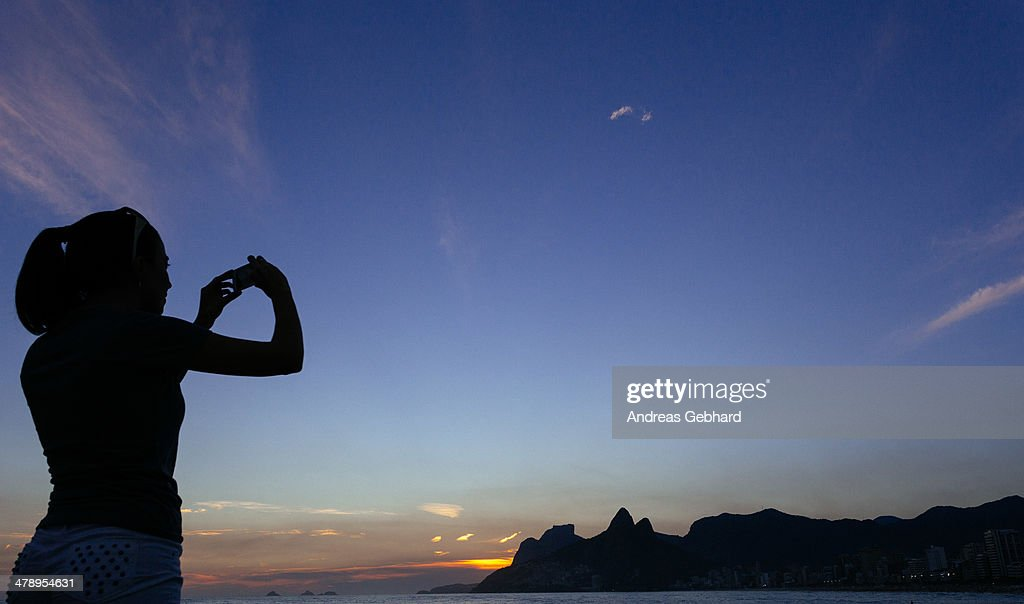 Silhouette of a woman taking a picture of sunset on Ipanema beach on her phone.