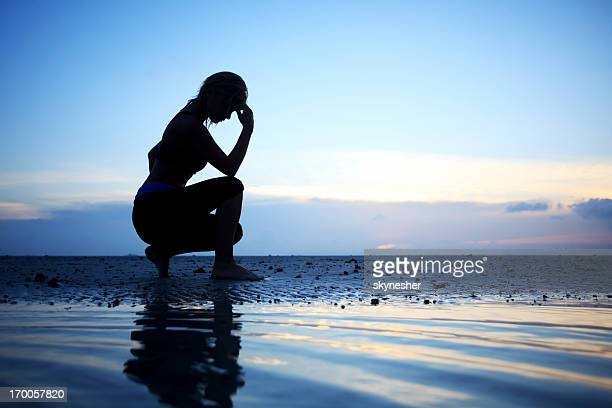 Silhouette of a woman thinking on the beach.
